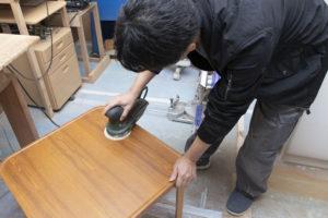 男性がテーブルを削っている